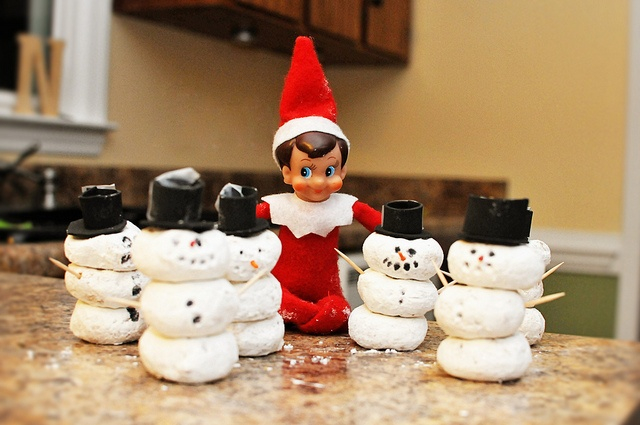 Elf making donut snowmen