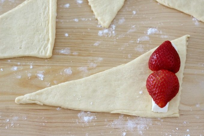 Place two strawberries on the cream cheese
