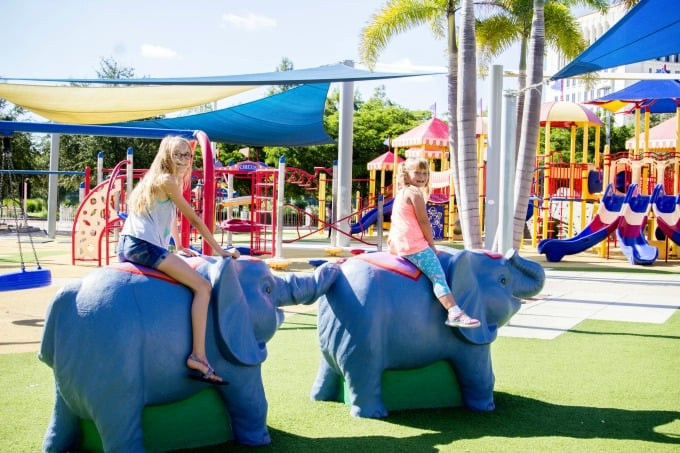 Girls playing on elephant statues