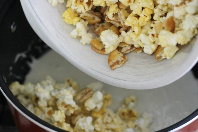 Add the popcorn snack ingredients to the melted marshmallows