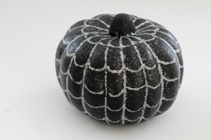 Use silver glitter glue to draw the web on your spiderweb pumpkin