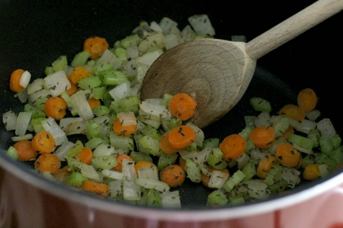 Add the onions, celery, garlic and herbs to the carrots and continue to cook