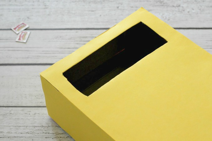 Cover the back of the box with yellow paper and cut another hole over the first one