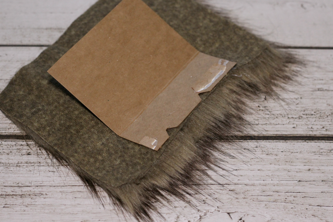Glue the cardboard to a larger piece of fur