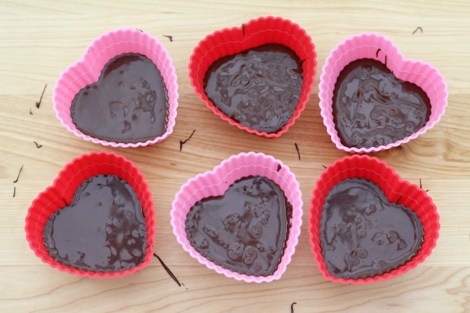 To make these Dark Chocolate Valentine Hearts, start by filling heart shaped silicone cups with chocolate