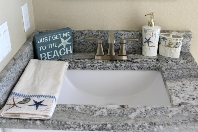 The beach sign added a nice touch to the coastal themed bathroom makeover