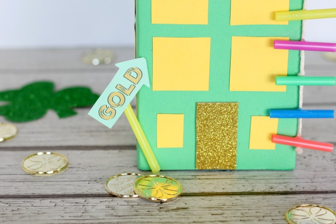 Glue the gold sign to the building so the leprechaun knows where to go.