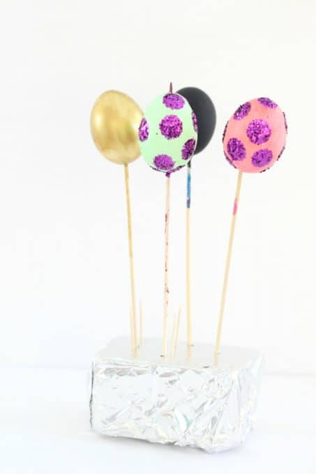 To dry your Easter eggs with nail polish, stick the end of the skewer in floral foam