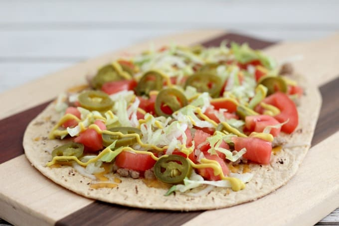 Top your cheeseburger flatbread pizza with lettuce, pickled jalapenos and mustard