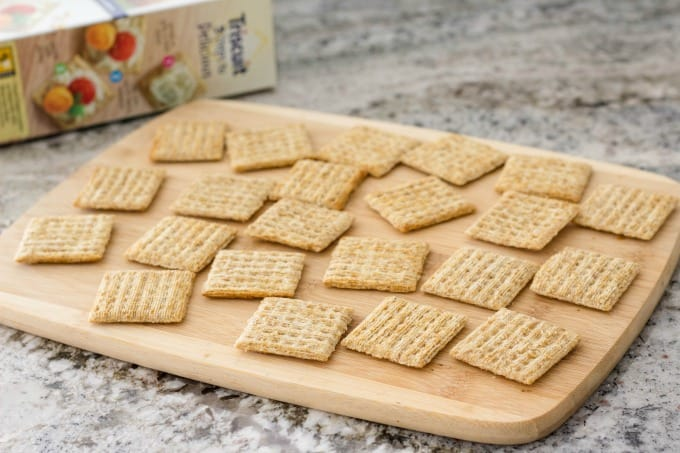 Spread Triscuit crackers on a tray or cutting board