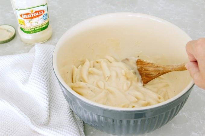 Adding alfredo sauce to pasta
