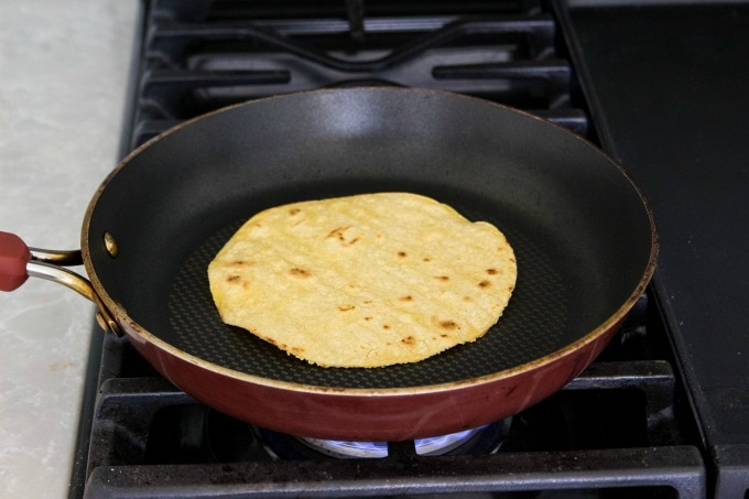 Warming a corn tortilla on the stove