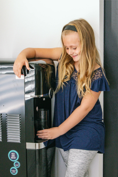 Keira grabbing water from the Primo Water Dispenser