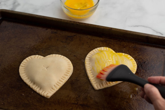 Brushing blueberry hand pies with egg wash