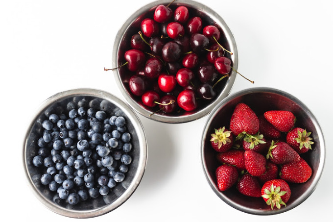 strawberries, blueberries and cherries in bowls