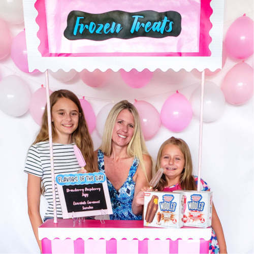 Mom and daughters at a frozen treat stand