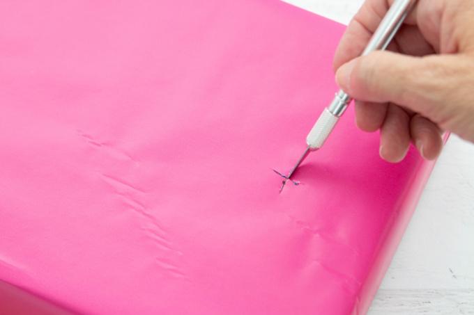 "Using a craft knife to cut an ""x"" in a cardboard box"