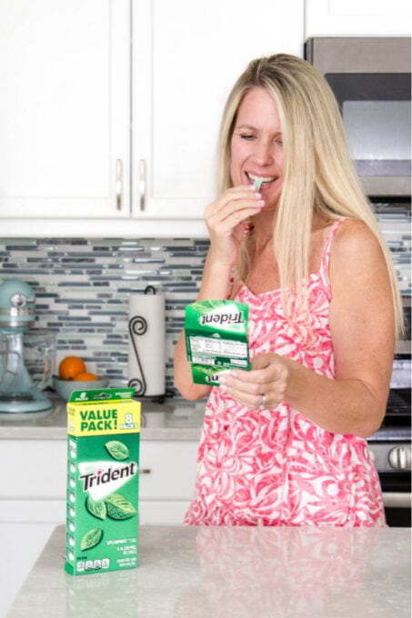 Person eating gum in a kitchen