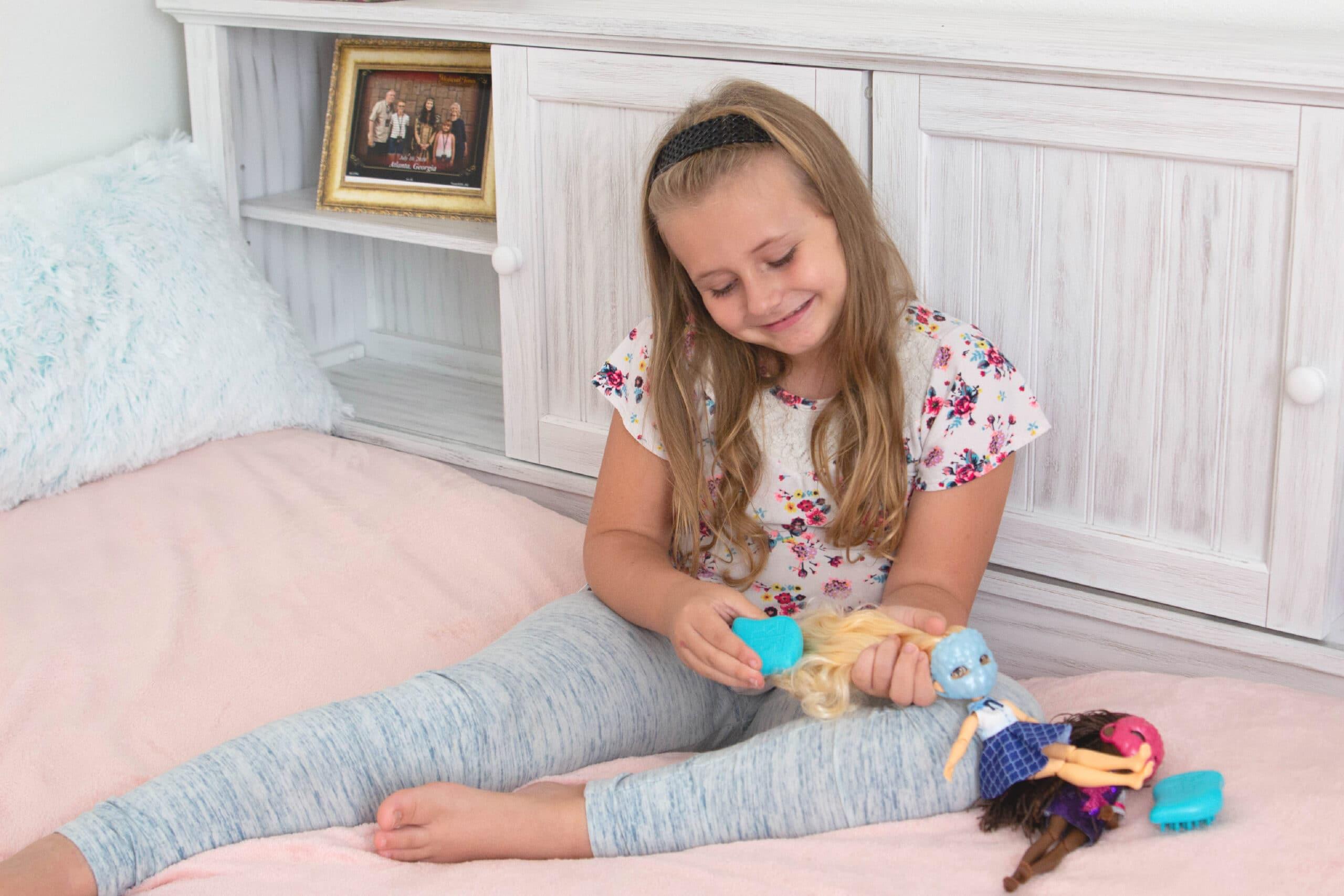 Little girl brushing dolls hair